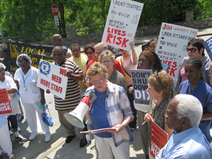 Beverly Moriarty (center, with bullhorn), RN at Dorothea Dix Hospital, speaks about the devastation that the planned closing of Dix will have. State Sen. Vernon Malone (lower right) attended the rally to show support for the concerns of the protesters.
